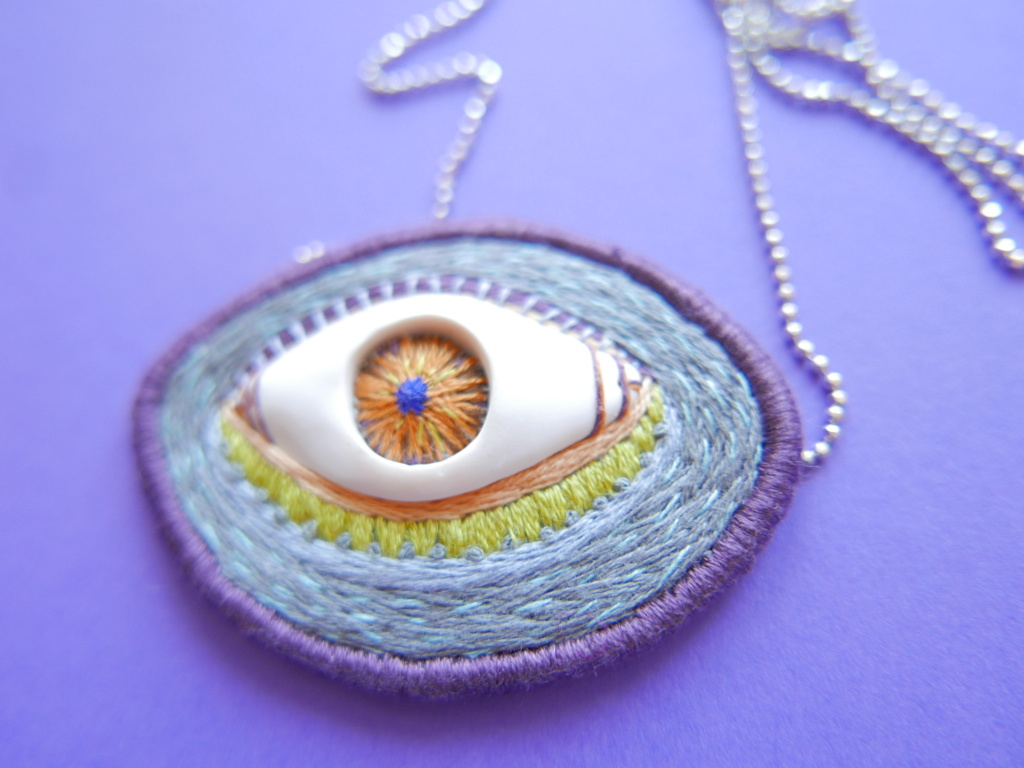 handmade necklace featuring polymer clay eye on a grey background