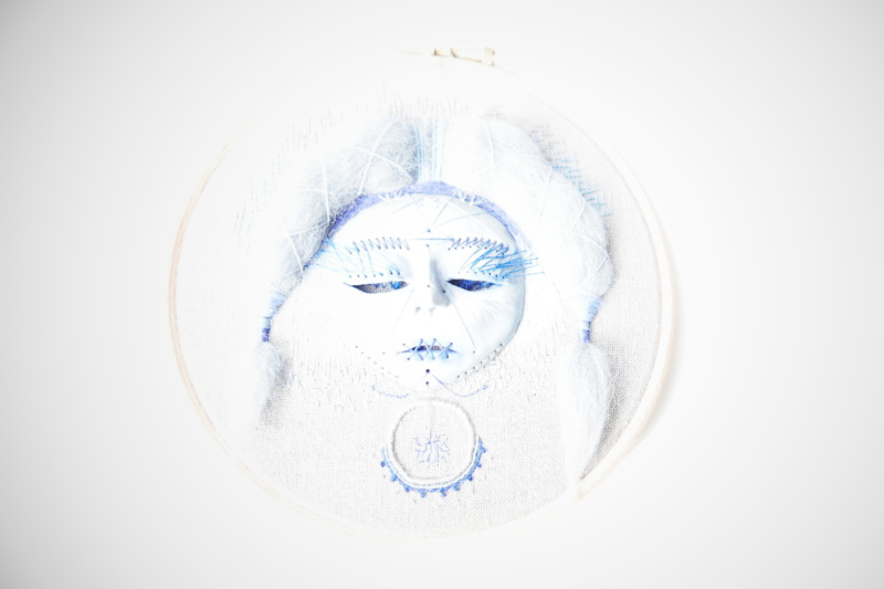 Hand embroidered face disappearing in light