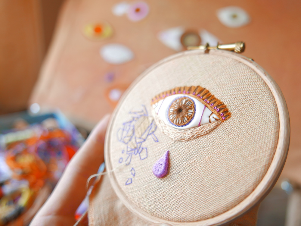 eye and teardrop on a wooden hoop