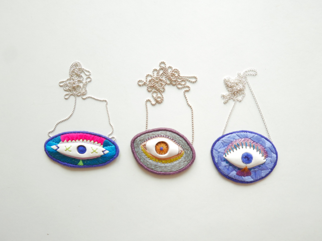 three hand embroidered necklaces with eyes